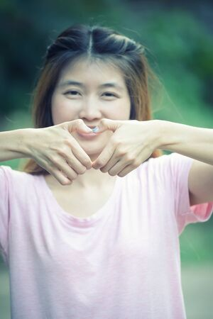 perception: asia smiling cheerful young woman making heart sign with hands, Positive human emotion expression feeling life perception attitude body language, happy concept