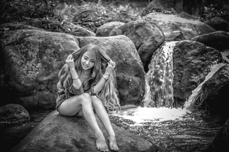 waterfall model: Asia Beautiful young girl sitting on the stone in water fall, black and white image