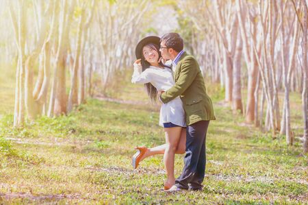 tenderness: asai young romantic man and woman standing and hugging each other with tenderness in the field. Young love concept. Stock Photo