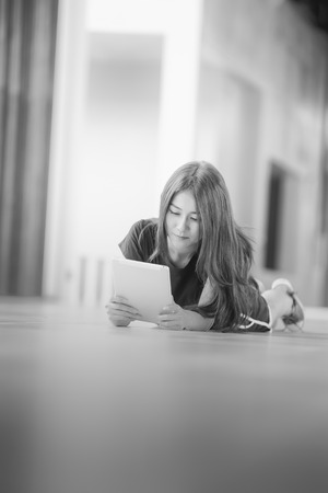 asia girl lying on floor and looking into tablet computer at home