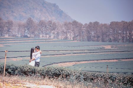 tenderness: asai young romantic man and woman standing and hugging each other with tenderness in tea plantation. Young love concept. Stock Photo