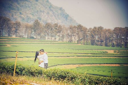 fondle: asai young romantic man and woman standing and hugging each other with tenderness in tea plantation. Young love concept. Stock Photo