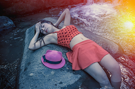 young add: Asia beautiful young sexy girl lying down on a rock in red clothes, add flare for mood and tone style Stock Photo