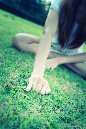 little finger: asia women lying with Hand showing little finger on green grass in park