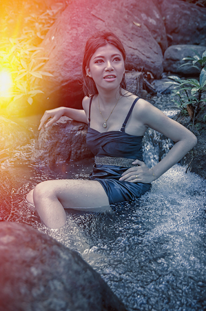 young add: Portrait of Asia Beautiful young  girl sitting in water fall, add flare for mood and tone style