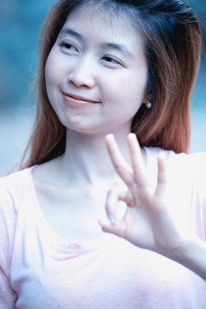 asia young cute woman showing OK