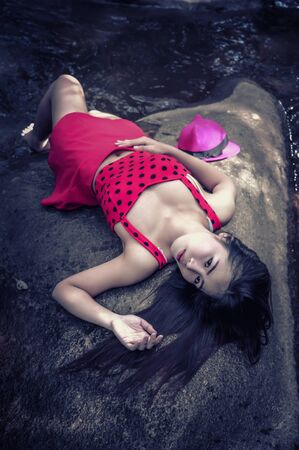 girl lying down: Asia beautiful young sexy girl lying down on a rock in red clothes
