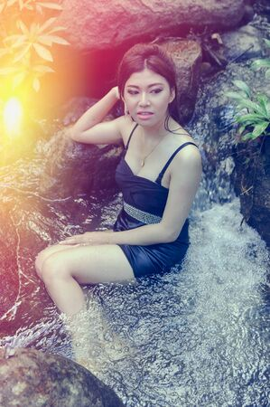 waterfall model: Portrait of Asia Beautiful young  girl sitting in water fall Stock Photo