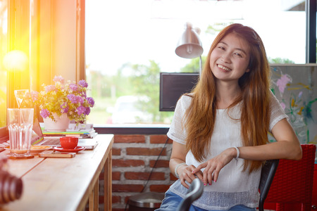 asia Attractive woman sitting on the couch at coffee shop
