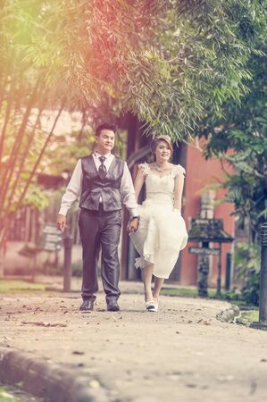 young add: couple in love. portrait of asia young stylish fashion couple posing on outdoor. wedding style, love concept, add flare and vintage effect Stock Photo