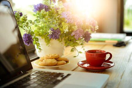 kopje koffie, koekjes en laptop op houten bureau in cafe, business concept
