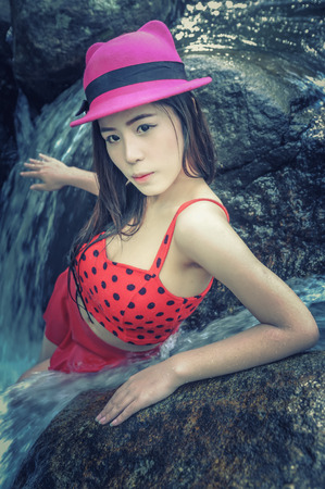 waterfall model: Asia sexy Beautiful young girl stand in the water fall, cross process effect for vintage style Stock Photo