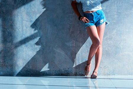 long sexy legs: long sexy legs of beautiful women jeans shorts fashion sunny day standing near to the wall, hipster style Stock Photo