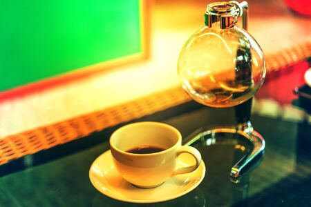 coffee cup and siphon vacuum coffee maker at shop