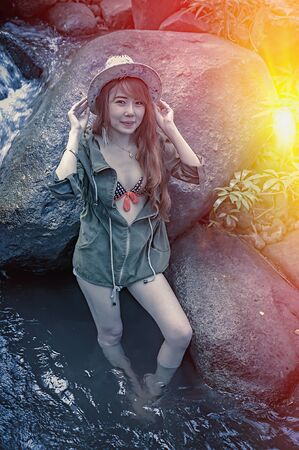 young add: Asia sexy Beautiful young girl stand in the water fall, add flare for mood and tone style