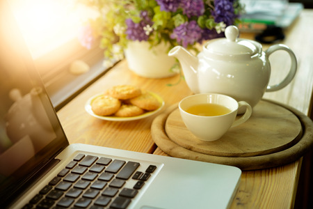 cup, tea pot ,cookies and laptop on wooden desk on cofe, business concept Standard-Bild