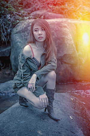 young add: Asia Beautiful young girl sitting on the stone in water fall, add flare for mood and tone style