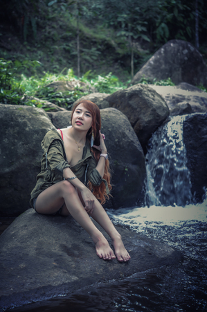 waterfall model: Asia Beautiful young girl sitting on the stone in water fall