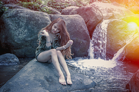 waterfall model: Asia Beautiful young girl sitting on the stone in water fall, add flare for mood and tone style