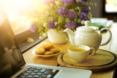 cup, tea pot ,cookies and laptop on wooden desk on cofe, business concept Stock Photo
