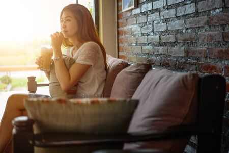 woman on couch: asia Attractive woman sitting on the couch at coffee shop