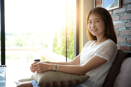 woman on couch: asia Attractive woman sitting on the couch at home