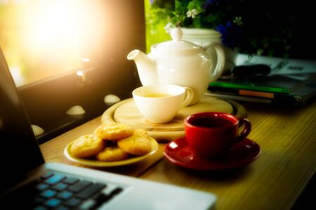 coffee cup, tea pot ,cookies and laptop on wooden desk on cofe, business concept