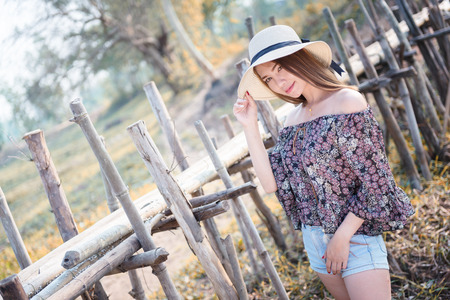 asia woman in Off  Shoulder shirt and short jeans with hat standing on nature Stock Photo