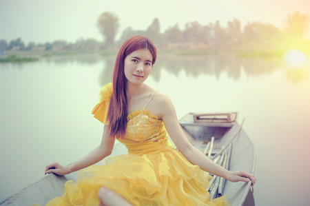 Portrait of Asia Beautiful woman in yellow dress sitting on boat