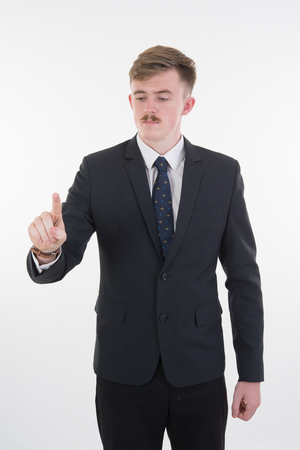a businessman in formal wear pushing forefinger screen on white background