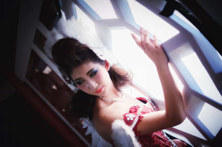 beautiful young woman with white angle wings of red dress posing near window Banque d'images