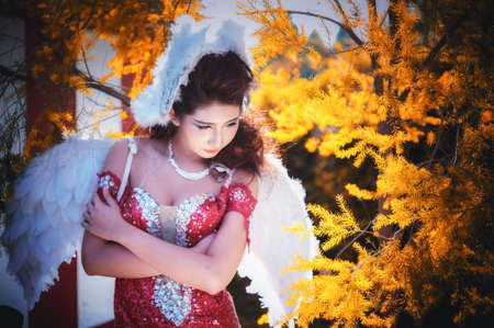 beautiful young woman with white angle wings of red dress posing in garden Banque d'images