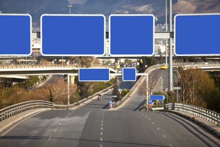 Cars on highway with blank directional road signs