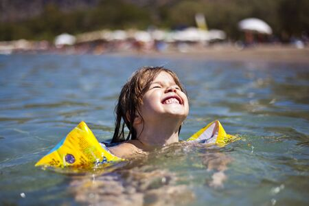 Portrait of happy child girl swimming in water Stock Photo
