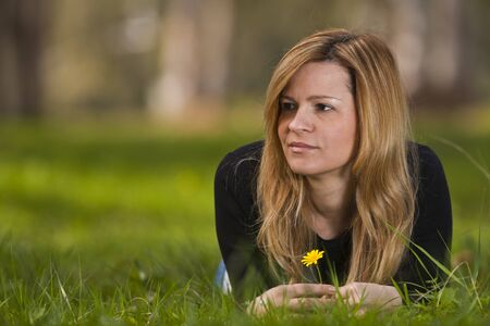 Young female sitting and smiling on grass  Stock Photo