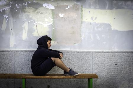 学校で一人で座っている小さな男の子は悲しくて、彼の顔を隠す 写真素材