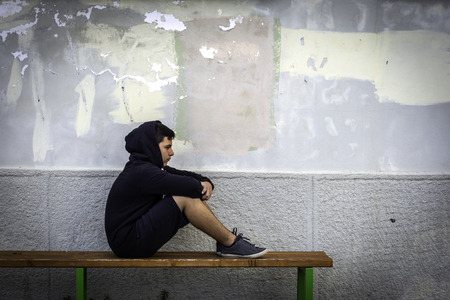 Kleiner Junge traurig, der allein in der Schule sitzt, verbirgt sein Gesicht Standard-Bild