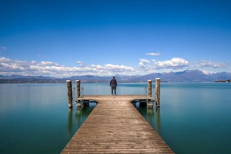 Hombre de pie sobre un embarcadero por el tranquilo lago de Garda, Italia Foto de archivo