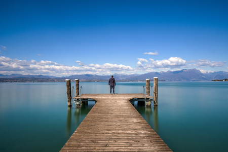 Man standing on a jetty by tranquil lake Garda, Italy Banco de Imagens