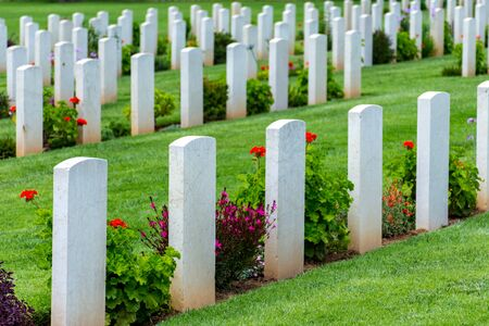Sun shining on gravestones with flowers on a beautiful and well cared War Cemetery in Greece