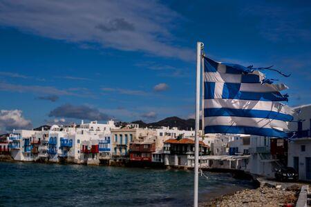 Greek flag waving in Little Venice bay of Mykonos town in Mykonos island in Greece