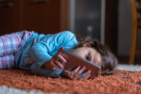 Cute little happy girl lying down on using looking digital smartphone mobile in the living room at home. family activity concept.