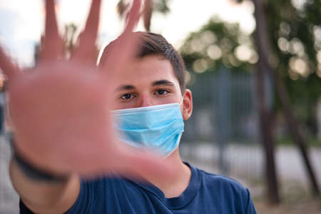 Teen boy wearing medical protective face mask during flu virus, making hand gesture Banque d'images