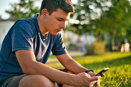 Teenage Boy Using Phone In Urban Setting Фото со стока