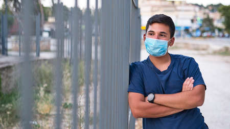 Young teen boy wearing face mask outdoor due to the Coronavirus Pandemic