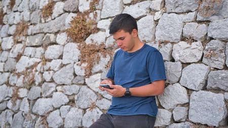 Teenage Boy Using Phone In Urban Setting Banque d'images