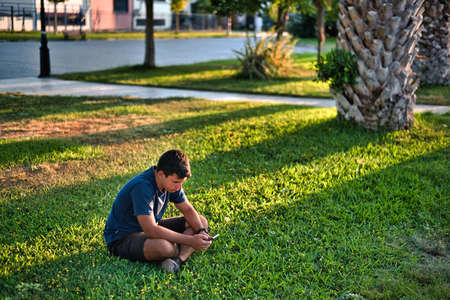 Teenage Boy Using Phone In Urban Setting, Sitting on Grass at sunset