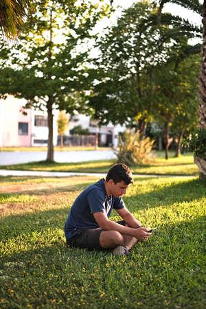 Teenage Boy Using Phone In Urban Setting, Sitting on Grass at sunset