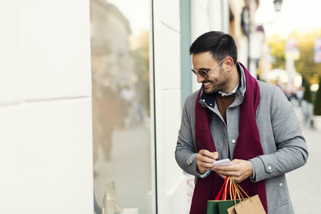 Handsome young attractive man looking at store window while shopping