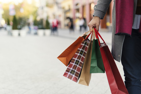Man holding shopping bags with presents on the street Stock fotó
